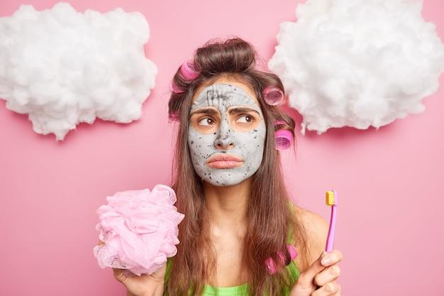 불쾌한 검은 머리 젊은 유럽 여성은 점토 마스크를 영양가있는 헤어 롤러를 적용하여 칫솔과 분홍색 벽 위에 절연 목욕 스폰지를 보유하고 있습니다.