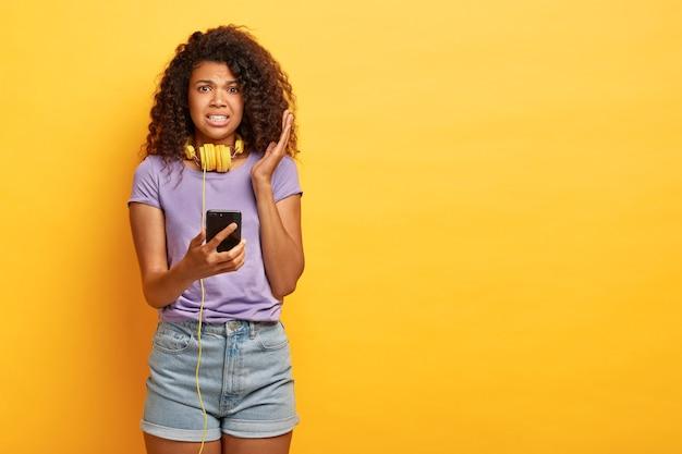 La donna riccia dalla pelle scura scontenta ascolta un messaggio vocale disgustoso in cuffia, tiene uno smartphone moderno, indossa una maglietta viola e pantaloncini di jeans, si erge contro il muro giallo dello studio, copia spazio