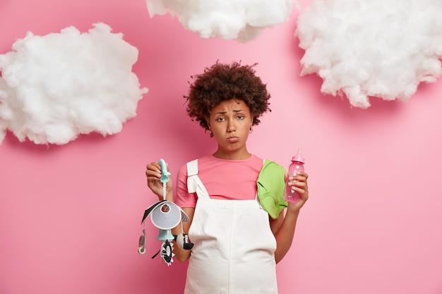 Donna riccia dalla pelle scura dispiaciuta con pancia incinta, tiene mobile, biberon, pagliaccetto, pose contro il muro rosa, nuvole bianche sopra. la futura mamma compra le cose necessarie per il bambino.