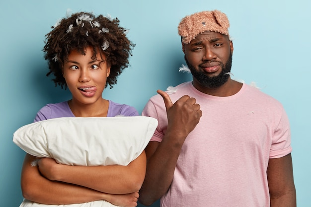 Displeased dark skinned guy points at funny afro american woman who crosses eyes and sticks out tongue, holds white pillow, has fun before going to bed. couple have late regime, need rest time