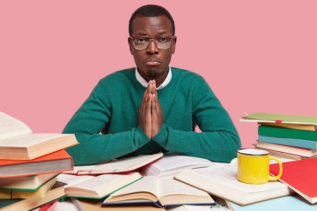 Displeased dark skinned man has sorrowful expression, keeps palms in praying gesture, believes in good luck while passing exam
