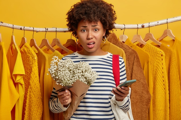 Displeased dark skinned woman poses in fashion store against clothes racks, has problems with paying online