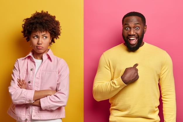 不機嫌な黒ずんだ女性が手を組んで立ち、喧嘩後に夫から顔を向け、気分を害する