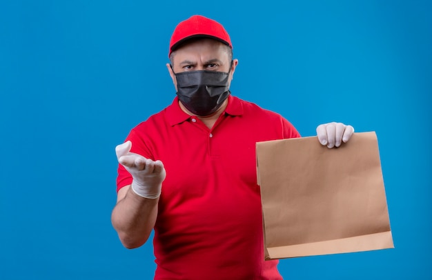 Displeased delivery man wearing red uniform and cap in facial protective mask holding paper package pointing with arm of hand to camera arguing over blue wall