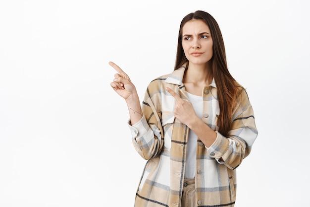 Cliente femminile dispiaciuto e dubbioso, guardando da parte e accigliato scettico, avendo dubbi con la qualità del prodotto, in piedi deluso contro il muro bianco