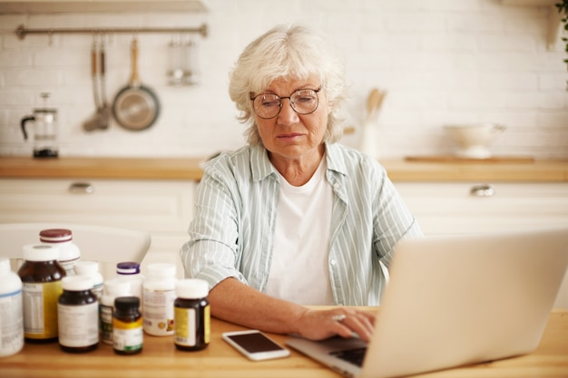 Недовольная пожилая европейская пенсионерка в круглых очках сидит на кухне, с презрением смотрит на бутылки с пищевыми добавками и набирает сердитый негативный отзыв на веб-сайте с помощью ноутбука