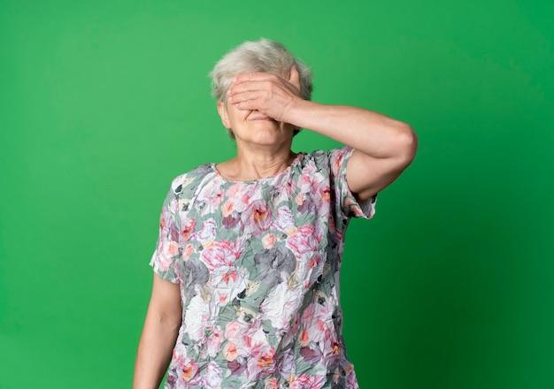 불쾌한 노인 여성이 녹색 벽에 고립 된 손으로 눈을 감고