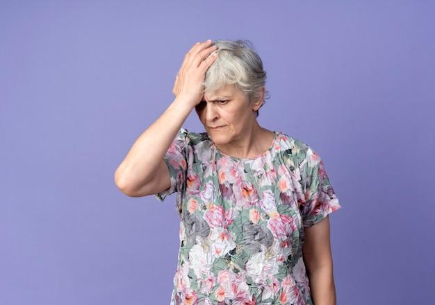 불쾌한 노인 여성이 보라색 벽에 고립 된 이마에 손을 넣습니다.