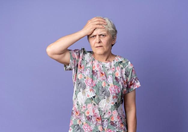 불쾌한 노인 여성이 보라색 벽에 고립 된 기대에 이마에 손을 넣습니다.