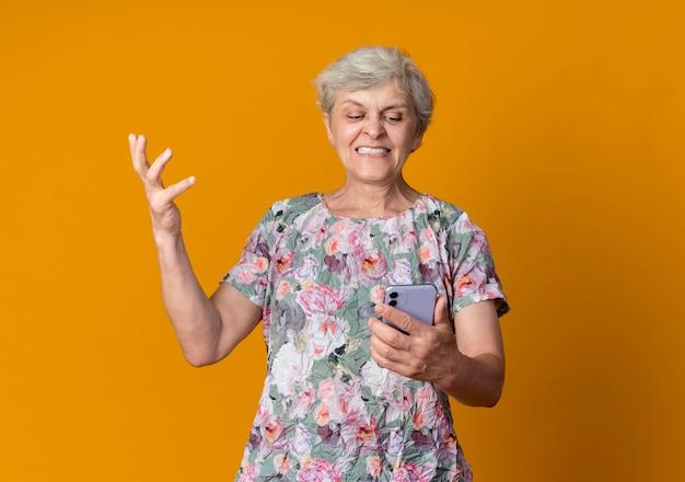 불쾌한 노인 여성이 손을 잡고 오렌지 벽에 고립 된 전화를보고 제기