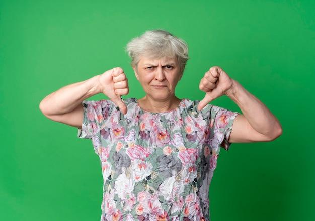 Недовольная пожилая женщина опускает палец вниз двумя руками, изолированными на зеленой стене