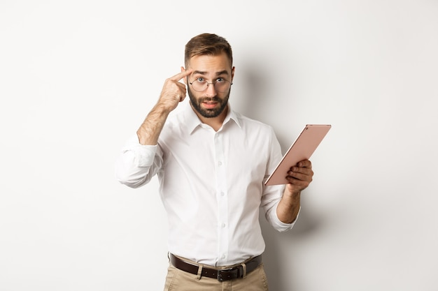 고용주가 직원을 꾸짖으며 디지털 태블릿에서 보고서를 확인하고 머리를 가리키며 실망한 표정으로 서 있습니다.