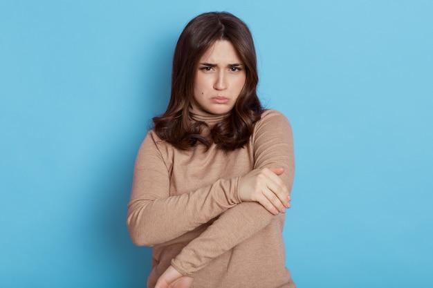 Femmina europea scontenta con un braccio doloroso, sorride e guarda con insoddisfazione