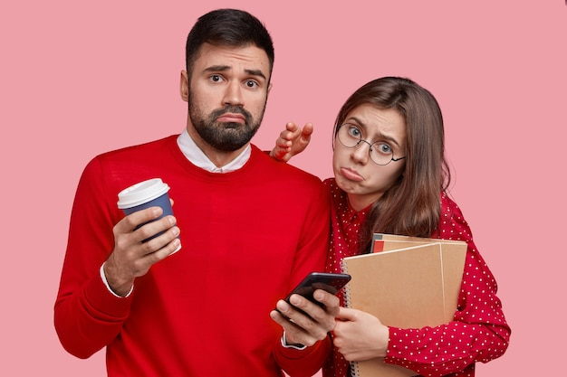 Displeased european lady and her boyfriend pose together, wear clothes in one colour have coffee break, use modern smart phone for online communication