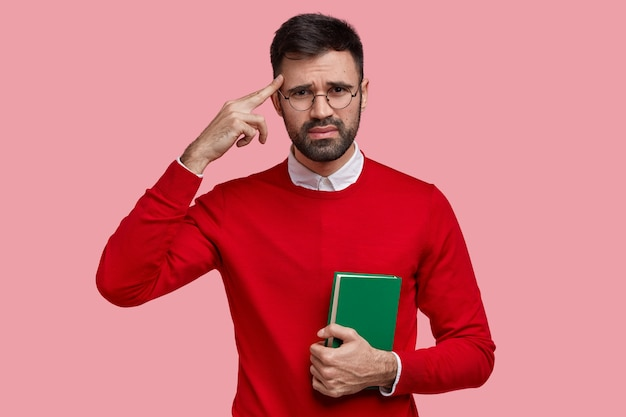Displeased european man keeps finger on temple, wears red sweater, carries green textbook, has unhappy facial expression