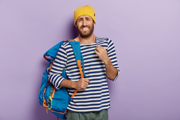 Displeased european man with upset expression, clenches teeth nervously, carries blue rucksack