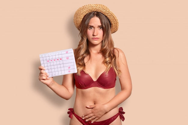 Displeased european woman feels pain during menstruation, keeps hand on bottom of belly, holds period calendar, wears summer hat and swimsuit, isolated over studio wall. female has periods