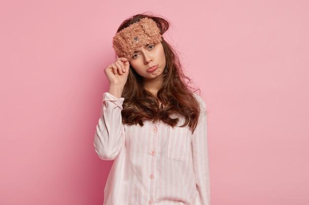 Недовольная европейская женщина носит маску для сна с медведем, пижаму, наклоняет голову