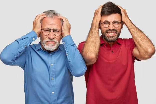 Padre scontento e giovane figlio adulto in posa contro il muro bianco