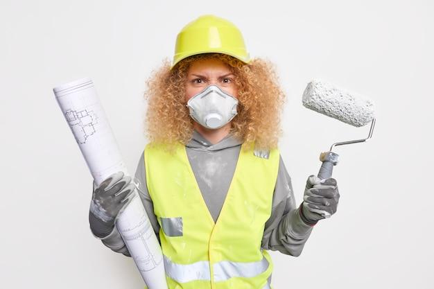 不機嫌な女性の建設現場のエンジニアは青写真を保持し、塗装ローラーは保護呼吸器のユニフォームを着用し、ヘルメットは建設プロジェクトの検査現場で働いています