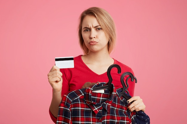Displeased female shopaholic takes variety of clothes on hangers, holds plastic card in hands, has unhappy look as being short of money, can`t buy new outfit. people, shopping, problems concept