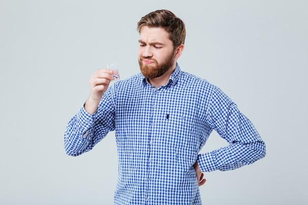 Недовольный хмурый бородатый молодой человек с бутылкой таблеток над белой стеной