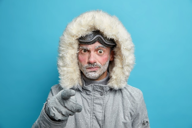 寒い季節にアウターを着て不満のせいで赤い顔のポイントを持った不機嫌な凍った男は、冬の冒険の準備をしています。