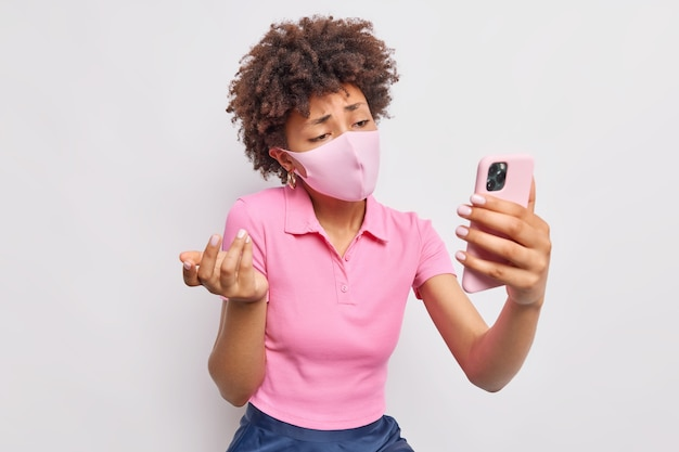 Недовольная разочарованная афроамериканка недовольно смотрит в камеру смартфона и грустит, находясь дома в самоизоляции, носит одноразовую маску, чтобы предотвратить распространение коронавируса, делает видеозвонок