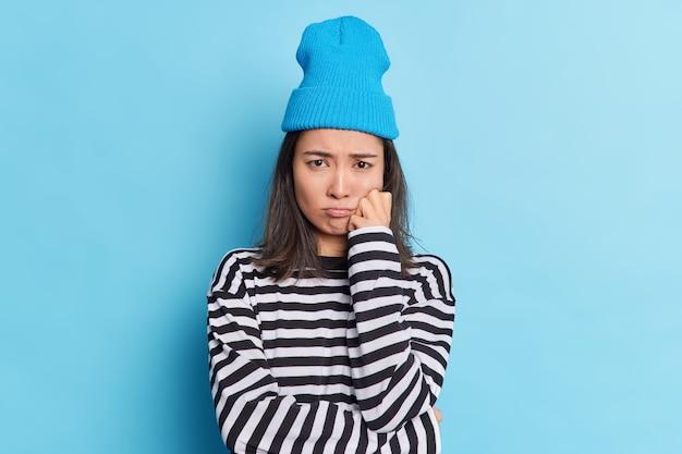 Недовольная разочарованная брюнетка азиатка обиделась, выражение лица грустно выглядит в плохом настроении
