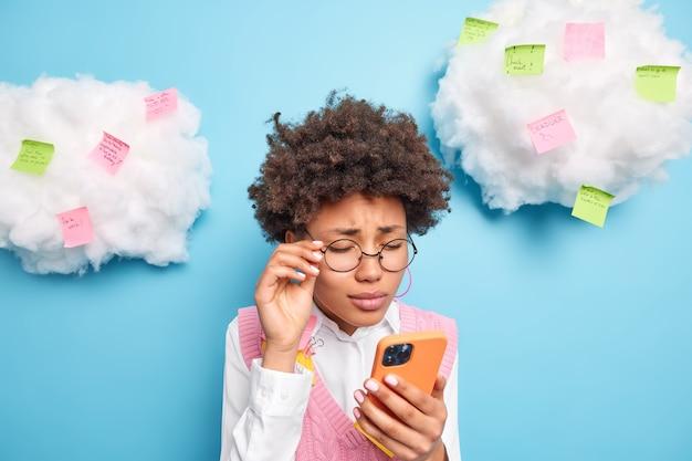 Impiegato femminile etnico infelice frustrato scontento deve preparare un rapporto urgente focalizzato sul display dello smartphone con espressione abbattuta indossa occhiali rotondi