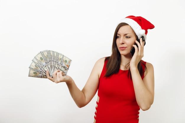赤いドレスとクリスマスの帽子をかぶった不機嫌な欲求不満の女性が携帯電話で話し、白い背景にお金の紙幣を持っています。ガジェットと現金が分離されたサンタの女の子。 2018年年末年始。