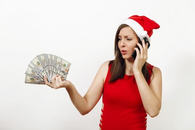 Раздосадованная разочарованная женщина в красном платье и рождественской шляпе разговаривает по мобильному телефону и держит денежные банкноты на белом фоне. девушка санты с гаджетом и изолированными наличными деньгами. новогодний праздник 2018.