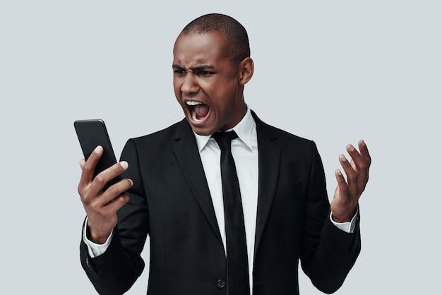 불쾌하다. 회색 배경에 서서 스마트 폰을 사용하고 인상을 찌푸리는 정장 차림의 분노한 젊은 아프리카 남자