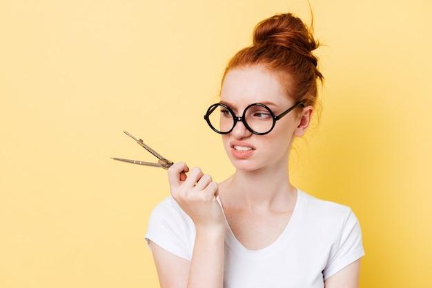 Displeased ginger woman in eyeglasses looking on dividers