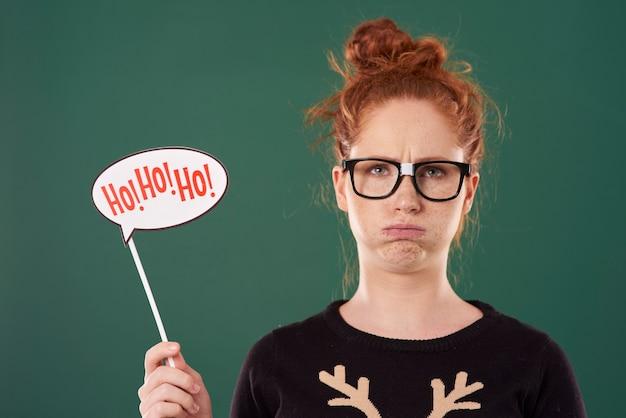 クリスマスのバナーを保持している不機嫌な女の子
