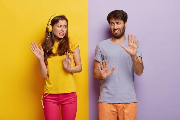 Fidanzata e fidanzato dispiaciuti fanno un gesto di rifiuto, provano avversione, sorridono