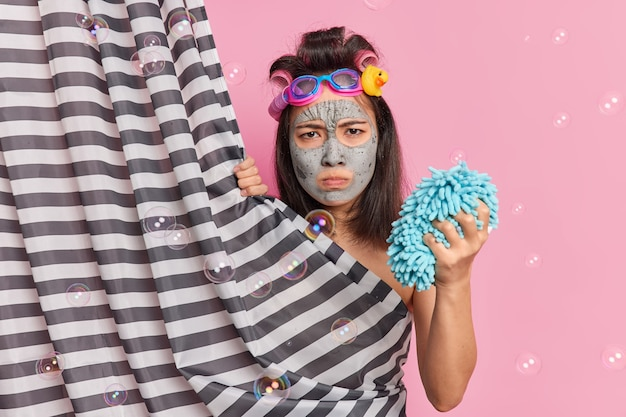 Displeased gloomy asian woman with dark hair makes hairstyle applies facial clay mask for skin rejuvenation holds shower sponge has angry mood poses behind curtain isolated on pink studio wall