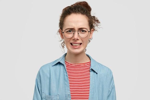 Недовольная мрачная дама хмурится, выражает негативные чувства, стиснет зубы
