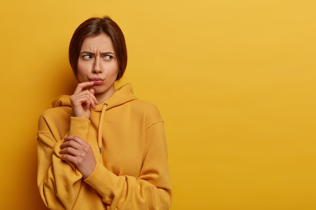 Displeased gloomy young woman thinks about something troublesome and upsetting, looks angrily aside, pouts lips, frowns face, dressed in casual hoodie, isolated on yellow wall. negative feelings