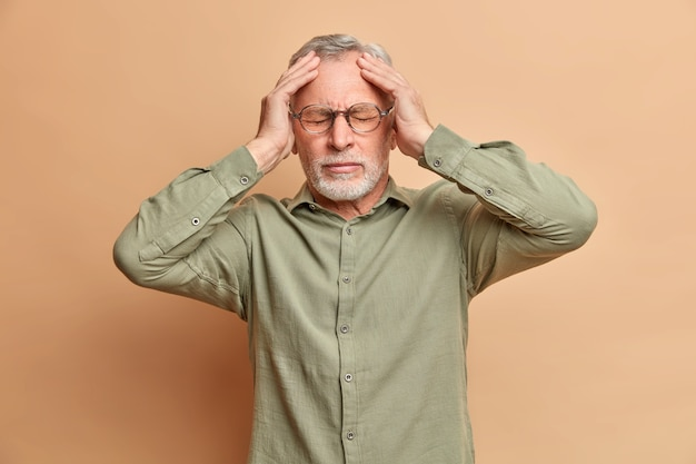 Displeased grey haired man suffers headache keeps hands on head to reveal pain needs painkillers has migraine after noisy party wears formal shirt isolated over brown wall