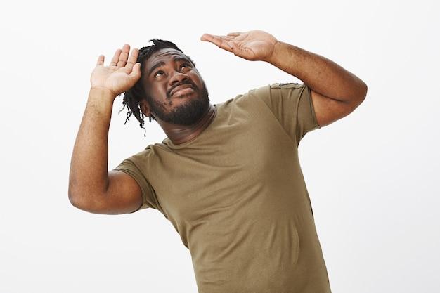 白い壁にポーズをとって茶色のtシャツを着た不機嫌な男
