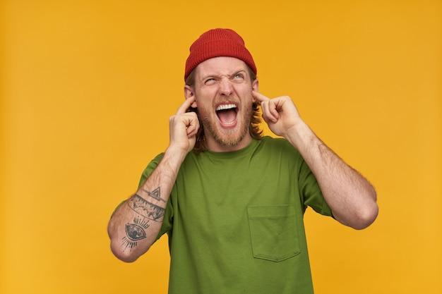 Недовольный парень со светлыми волосами и бородой. в зеленой футболке и красной шапке. имеет татуировку. закрой уши и крикни. раздражает шум. наблюдая за копией пространства, изолированной над желтой стеной