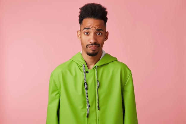 Scontento bel ragazzo dalla pelle scura in impermeabile verde, alzando il sopracciglio con aria interrogativa, dubbi e guarda la telecamera si leva in piedi su sfondo rosa.