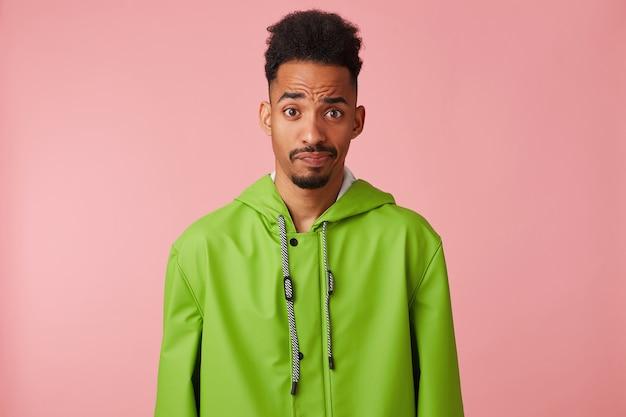 緑のレインコートを着た不機嫌なハンサムな暗い肌の男は、疑わしい眉を上げ、疑って、ピンクの背景の上に立っているカメラを見ます。