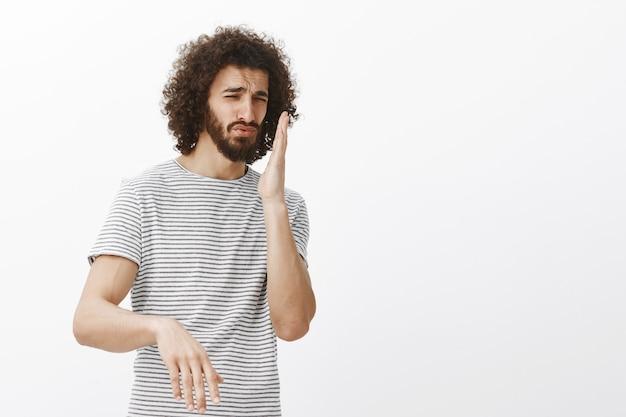 줄무늬 티셔츠에 불쾌한 잘 생긴 히스패닉 남자, 코 근처에 손바닥을 흔들며 찡그린 얼굴, 끔찍한 냄새 냄새 맡음