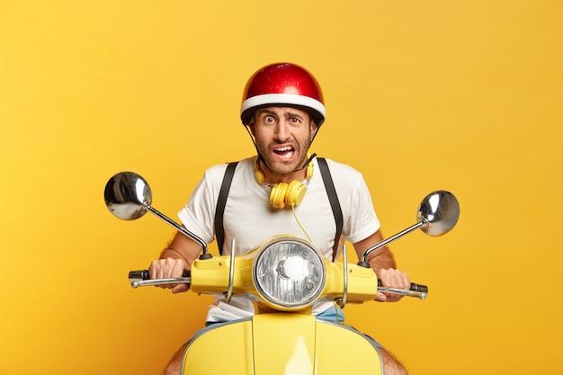 Autista maschio bello scontento su scooter con casco rosso