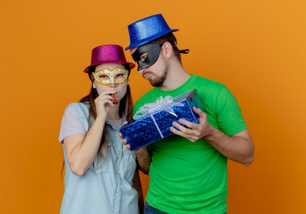 Displeased handsome man in blue hat wearing masquerade eye mask holding gift box looking at joyful young girl wearing pink hat and masquerade eye mask blowing whistle looking at front