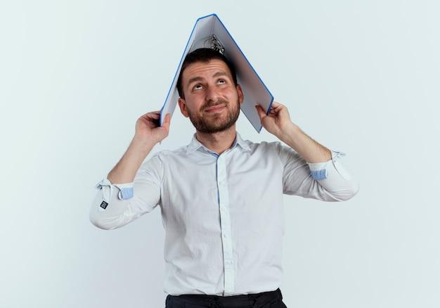不機嫌なハンサムな男は白い壁で隔離の頭の上にファイルフォルダを保持します