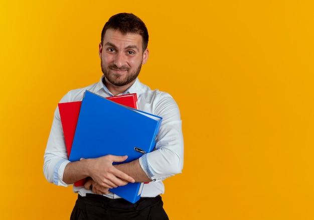 不機嫌なハンサムな男はオレンジ色の壁に隔離されたファイルフォルダを保持します