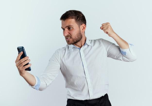 不機嫌なハンサムな男は、白い壁に隔離された電話を見て拳をパンチする準備ができています